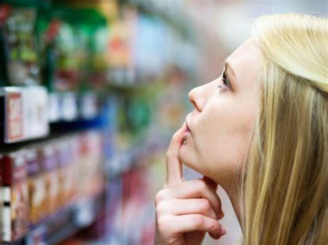 Une consommatrice qui regarde tous les produits dans une allée d'un supermarché avec une expression désorientée.