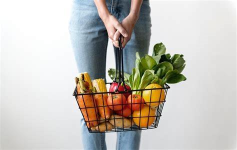 Une personne tenant un panier de fruits et légumes bios frais sans emballage.