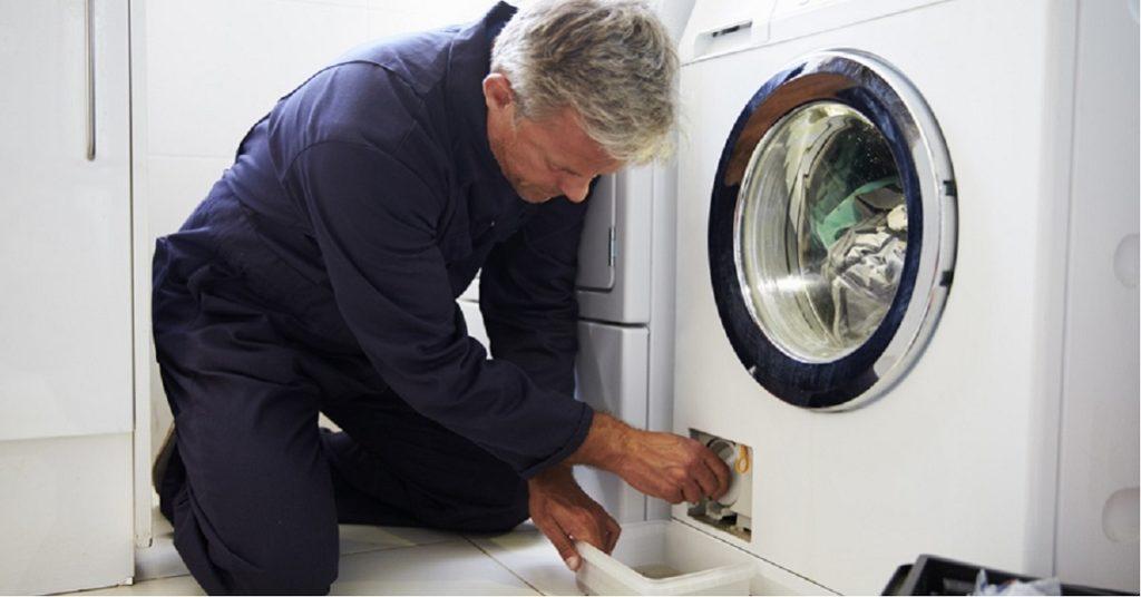 Un plombier réparant un lave linge qui fuit