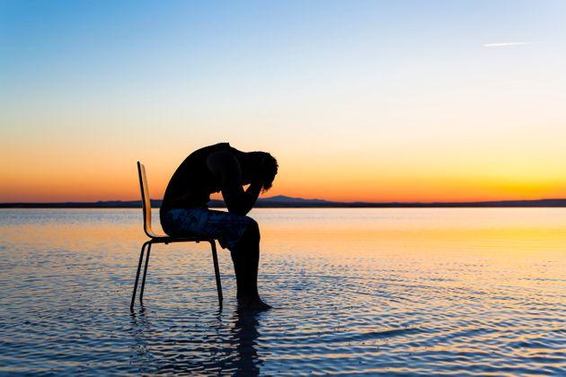 Un homme est assis sur une chaise  sur la mer. Celui ci est entouré d'un couché de soleil est d'un paysage idyllique. Pourtant, il se morfond, il met la tête en bas et tient sa tête avec ces mains.