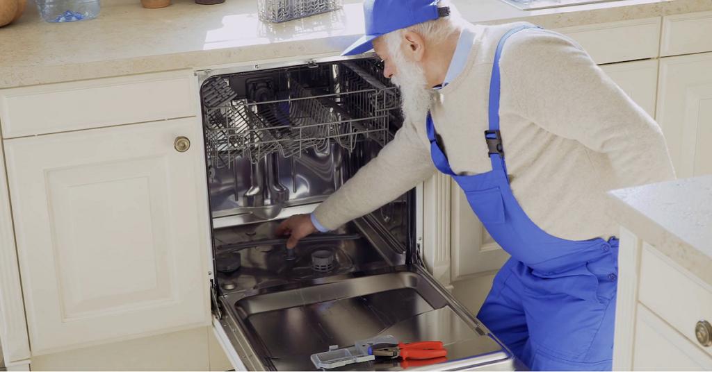 Un vieil homme en bleu entrenant un lave-vaisselle